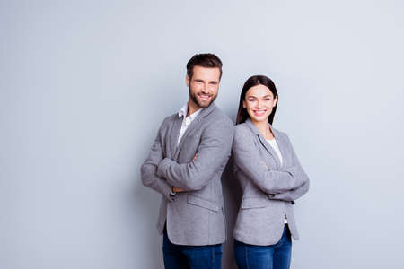 Photo pour Concept of partnership in business. Young man and woman standing back-to-back with crossed hands against gray background - image libre de droit