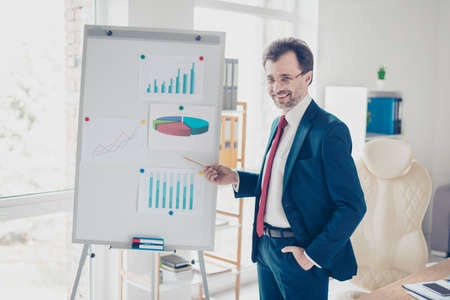 Smiling successful businessman is reporting with the flip chart in office. He is in blue suit, glasses and red tie