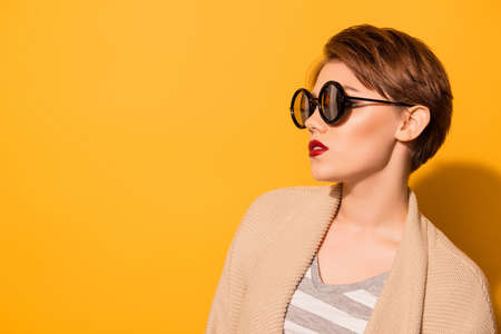 Fashionable look of the model in stylish sunglasses and casual clothes on the bright yellow background