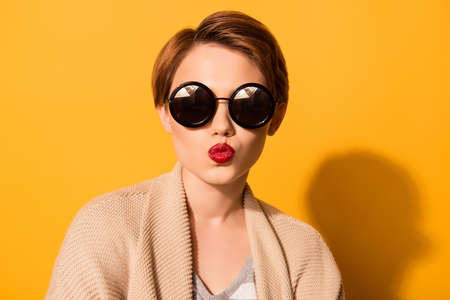 Foto de Fashionable young cute girl in trendy sunglasses sends a kiss  against bright yellow background - Imagen libre de derechos