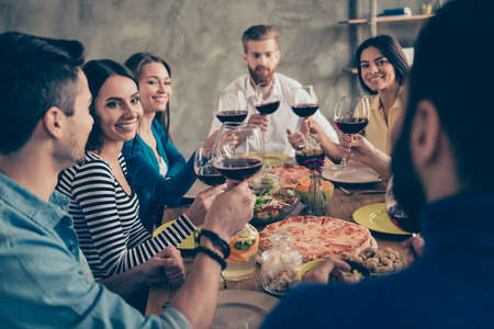 Photo pour Cheers! Friends got together by table with delicious food with glasses of red wine to celebrate a special occasion - image libre de droit