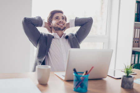 Foto de Dreaming young bearded entrepreneur is resting in front of laptop at his work station. He is happy, smiling and looking above - Imagen libre de derechos