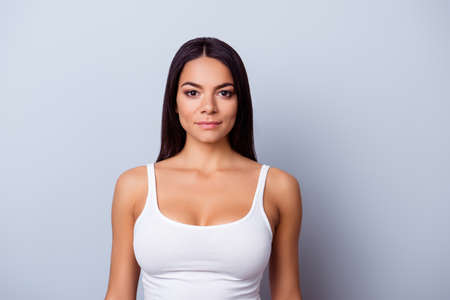 Photo pour Portrait of a young latino american mulatto girl. She is in a casual white singlet standing on the pure light blue background - image libre de droit