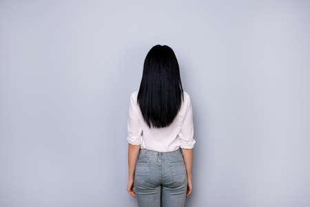 Foto de Back view of brunette lady in casual white outfit, jeans, standing still on pure light grey background - Imagen libre de derechos