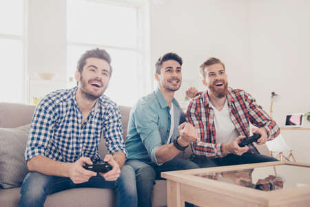 Photo pour Who will win? Competition of guys playing car race. Excited friends are playing games  indoors at home, sitting on cozy beige sofa and enjoying themselves. They have great and fun time - image libre de droit