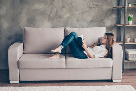 Relaxed young lady is studying, lying on the cozy beige couch in living room at home, so nice modern interior, so comfortable atmosphere for study and work