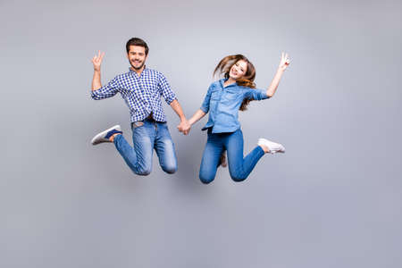 Photo pour Cheerful and playful couple in casual outfits are jumping and gesturing peace signs indoors, smiling, posing - image libre de droit