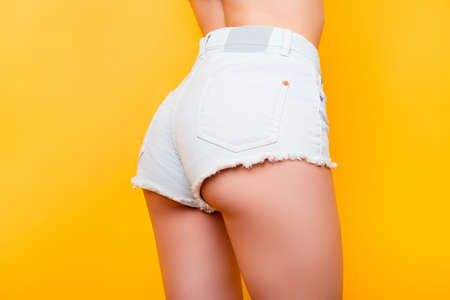 Back view of sexy girl showing her butt in tight white jeans shorts on bright yellow background. So fit and hot!