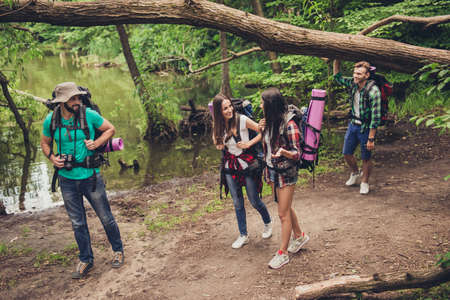 Trekking, camping and wild life concept. Four best friends are hiking in the spring woods, ladies are talking and laughing, all are excited and anxious in jungle trail