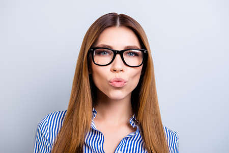 Kiss for you! Success and beauty concept. Close up of playful young business lady in formal wear, standing at the pure background isolated with pouted lips