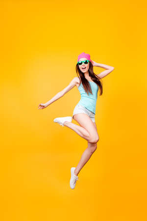 Photo pour Girlish, funky, happiness, dream, fun, joy, summer concept. Very excited happy cute asian teen is jumping up, in summer outfit, sun glasses, hat, on bright yellow background - image libre de droit