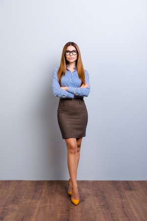 Full size photo of elegant business lady lawyer in strict outfit and glasses, standing in flirty pose with crossed hands and legs. She looks so sexy and tempting