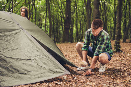 Close up of a young blond male tourist setting up a green tent in forest, on a fallen brown leaves, in a casual comfortable wear, green trees behind