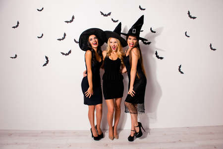 Full length of three terrifyng mysterious emotional flirty dark mistress monsters in elegant costume clothing, with bright red lips, long wizard headwears, standing posing on white wall background