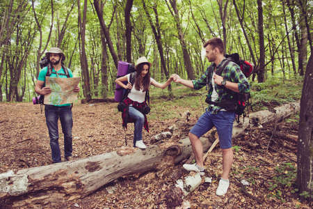 Trust, love, support, help, friendship concept. Three friends are hiking in the spring woods, the guy is holding lady`s hand, bearded man in hat is studying the map