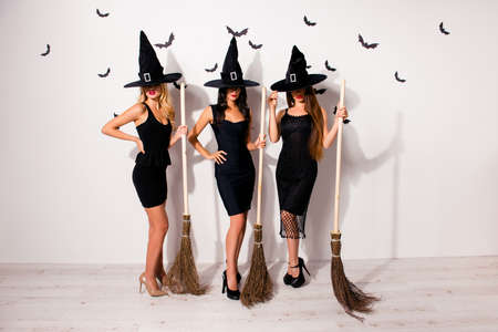 Full length of group of three mysterious hidden mistress vampire monsters in elegant costume clothing, with bright red lips, long wizard headwears, serious, with covered devil eyes, with brooms