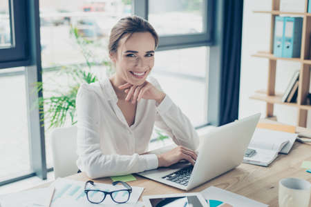 Foto de Development, authority, feminity concept. Pretty business woman is sitting at her light modern work station, checking e mails in front of digital device, smiling and looking at camera - Imagen libre de derechos