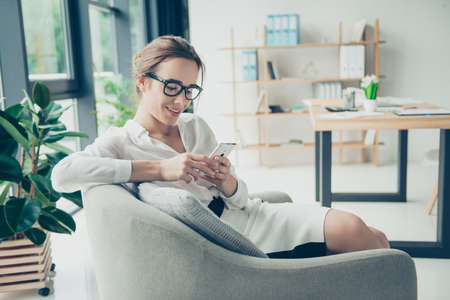 Comfort and cozy place. Young cute lady in black trendy eyewear is browsing on her phone, sitting on armchair. She is in formal outfit, smiling, sitting in relaxing atmosphere in office