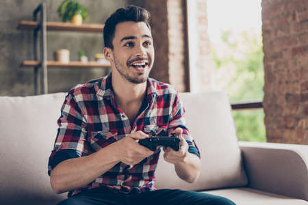 Photo pour Close up of attractive hipster with bristle and toothy grin, holding joy stick and playing videogames on tv at vacation, sits at home on the cozy couch, successful, he is winning at crazy car race - image libre de droit
