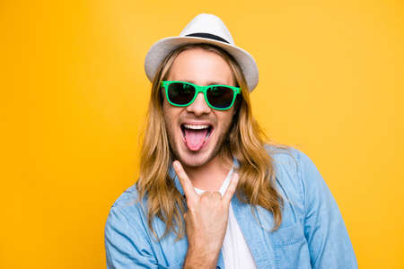 Foto de Rock n roll babe! Closeup portrait of cool young playful hipster man in casual outfit showing his tongue and rock on gesture, standing over yellow background - Imagen libre de derechos