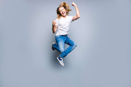 Joyful happy excited young man with blonde long hair is screaming and jumping up with raised fists, isolated on grey background