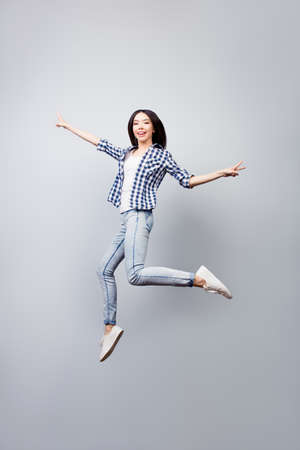 Photo pour Beautiful joyful girl dressed in checkered shirt and jeans is jumpig up and showing v-sign, she is isolated on grey background - image libre de droit