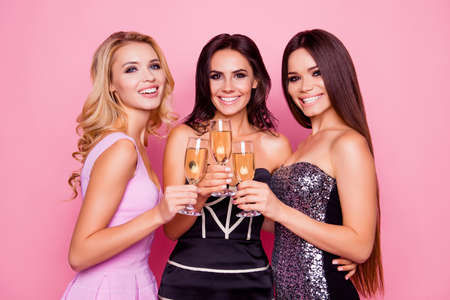 Foto de Portrait of three amazing, cute, pretty, astonished girls in luxury short dresses holding glasses with champagne, spending  together new year party, standing over pink background - Imagen libre de derechos
