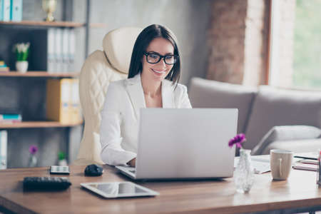 Photo for Beautiful confident smart stunning elegant journal editor is typing on laptop a new article for magazine, she is sitting at her workplace - Royalty Free Image