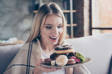 Photo pour Diet is finished! Wow! Yum-yum! beautiful excited happy glad joyful woman is going to eat sweets, donuts and macaroons at the weekend, she is alone and nobody sees her! - image libre de droit