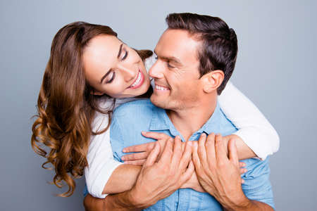 Foto de Close up portrait of mature, adult, attractive, lovely, cute, sweet spouses, charming woman hugging man from back and they looking to each other, holding hands over grey background - Imagen libre de derechos