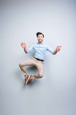 Photo pour Happy, young, bearded, attractive handsome, smiling man in classic outfit  jumping in air putting his feet together over grey background - image libre de droit