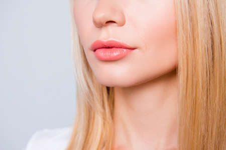 Close up photo of woman's skin with expression wrinkles, blonde hair and lips with moisturizing balm on them. She is isolated on grey background