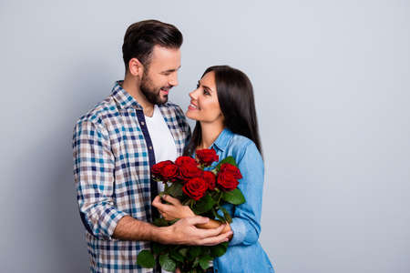 Photo pour Beautiful, happy, positive couple embracing, looking to each other, holding bouquet of red roses over grey background, 14 february, young, cute family going to be parents - image libre de droit