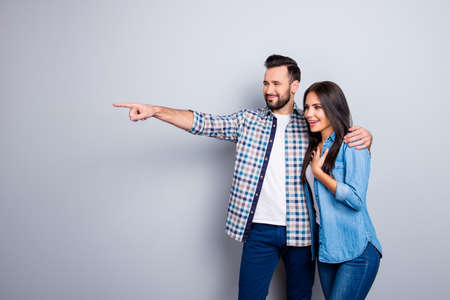 Photo pour Bearded, smiling man embracing his excited, charming  girlfriend and showing to her something with forefinger over grey background - image libre de droit