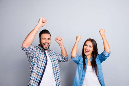 Photo pour Portrait of young caucasian, sweet, foolish, attractive, lovely, cute, crazy, successful partners celebrating victory with raised fists, screaming, shouting over grey background - image libre de droit