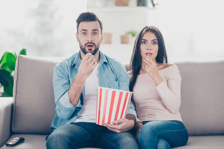 Photo pour Unexpected turn of events in a film! Two charming beautiful funny man with bristle clothed in jeans denim outfit and attractive dressed in sweater and jeans woman are pop-eyes surprised watching tv - image libre de droit