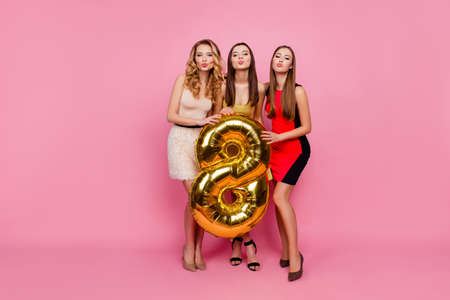 Photo pour Full length portrait of three pretty, funny girls, blowing kiss to the camera, celebrating, women's day, eight march, having gold balloon, standing over pink background - image libre de droit