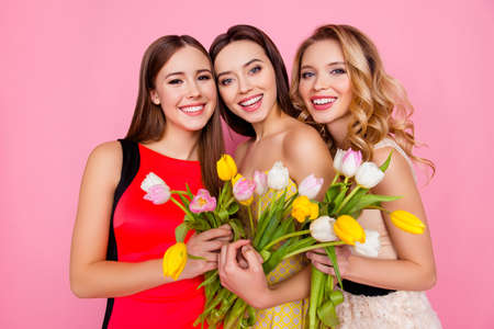 Photo pour Pretty, nice, charming, successful trio of girls in dresses with hairstyle, having colorful tulips in hands, looking at camera, celebrating 8-march, women's day, standing over pink background - image libre de droit