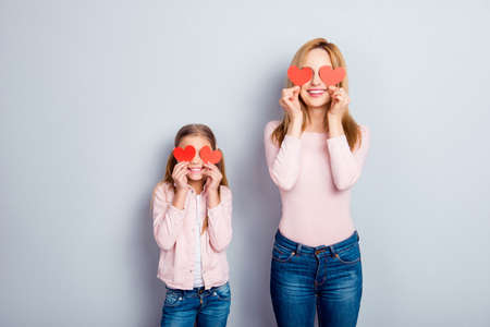 Foto de Attractive, nice, cute, sweet, charming daughter and mom, mum standing over gray background, holding four small paper hearts on eyes place, smiling, having fun - Imagen libre de derechos