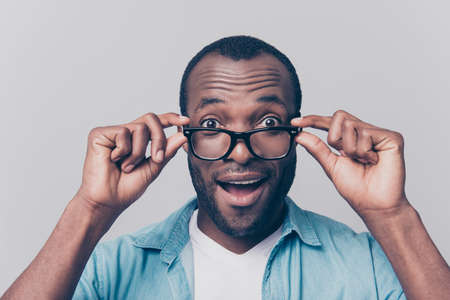 Foto de Omg! I can see you perfectly!  I have good vision! Close up portrait of excited cheerful glad satisfied surprised afro guy taking off his unnecessary glasses isolated on gray background - Imagen libre de derechos