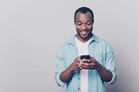 Photo pour Portrait of handsome excited cheerful joyful delightful curious guy wearing casual jeans denim shirt sending and getting messages to his lover isolated on gray background - image libre de droit