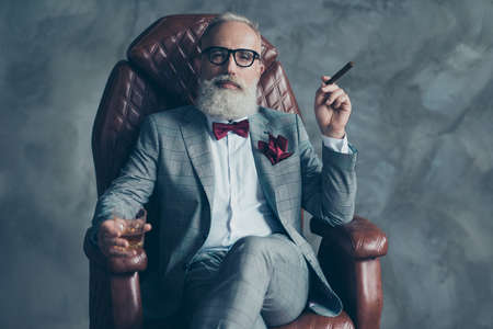 Foto de Cool man in glasses, hold cigarette,  glass with brandy, in formal wear, tux with red bowtie and pocket square, sit in leather chair over gray background, looking to the camera, shares, stock, money - Imagen libre de derechos