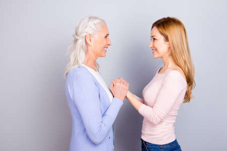 Foto de Two charming adorable wonderful dreamy darling dear beautiful cheerful excited joyful mama and kind friendly attentive sensitive daughter holding hands looking at each other isolated gray background - Imagen libre de derechos