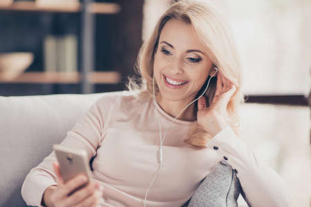 Foto de Close up portrait of attractive pretty woman  siting on couch in living room, having, using earphones, holding smart phone, listening music, looking at screen of telephone in hand - Imagen libre de derechos