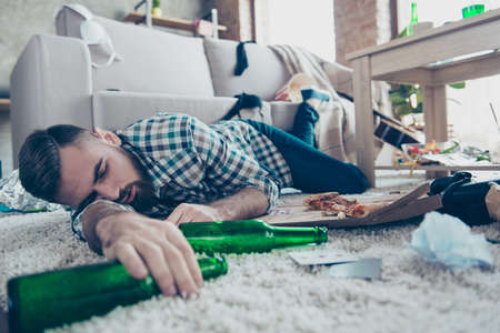 Photo pour Sick drunk dreamy bearded guy clothed in checkered shirt and denim jeans is sleeping on the floor with an empty bottle in hand - image libre de droit
