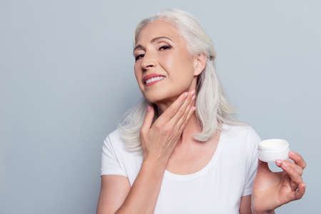 Foto de Mature adult senior woman with gray hair is taking care about her face and neck, she is smearing natural night cream using hand before going to bed, isolated on gray background - Imagen libre de derechos