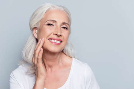 Foto de Charming, pretty, old woman touching her perfect soft face skin with fingers, smiling at camera over gray background, using day, night face cream, cosmetology procedures - Imagen libre de derechos
