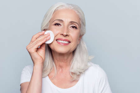 Excited cheerful confident lovely beautiful mature woman is using a cotton pad with micellar water for removing make up from face, isolated on grey background, copy-space