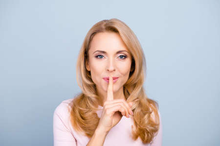Foto de Portrait of pretty, charming, mysterious, sexy, attractive woman holding forefinger on mouth, asking to keep silence - Imagen libre de derechos