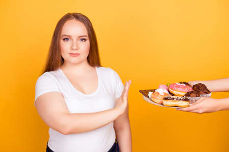 Photo pour Will-powered woman wearing white tshirt is refusing to consume tasty delicious sweets on a plate, isolated on bright yellow background - image libre de droit